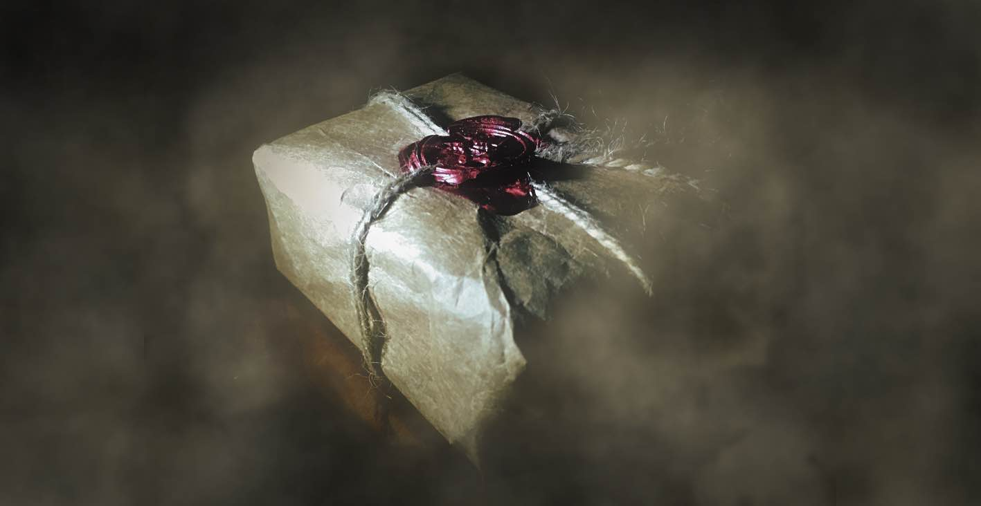 A mysterious package wrapped in brown paper, tied with twine with a red wax seal